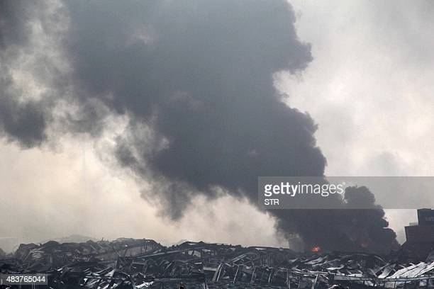 Smoke rises amid mangled wreckage at the site of a series of explosions in Tianjin on August 13 2015 A series of enormous explosions at an industrial...