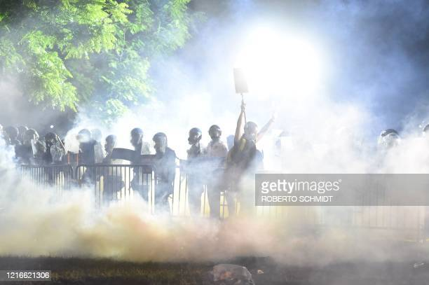 Smoke rises around a protester holding up their hands in front of a row of police during a demonstration against the death of George Floyd at a park...