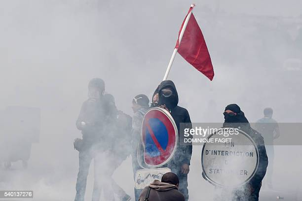 Smoke rises around masked protesters during a demonstration against proposed labour reforms in Paris on June 14 2016 Twentysix people were hurt and...