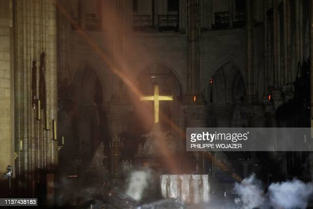 TOPSHOT Smoke rises around the alter in front of the cross inside the NotreDame Cathedral as the fire continues to burn on April 16 2019 in the...