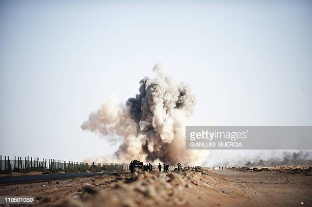 Smoke rises as a Libyan jet fighter drops a bomb on anti Libyan government fighters' position on the outskirt of the eastern oil port town of Ras...