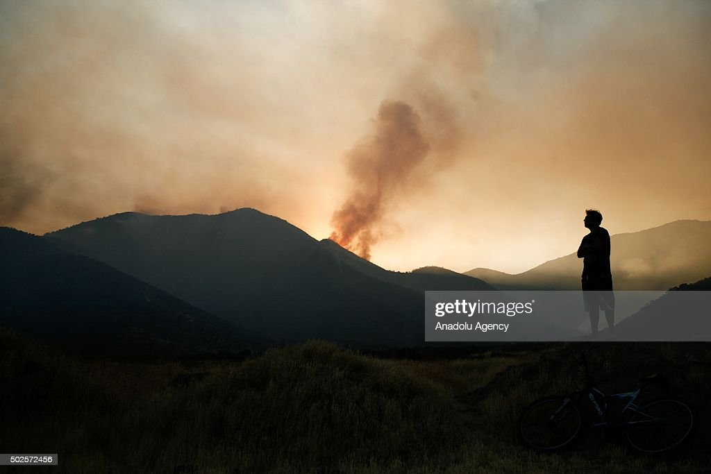 Smoke rises as fire affects Chicauma hills of the commune of Lampa in Santiago, Chile on December 26, 2015.