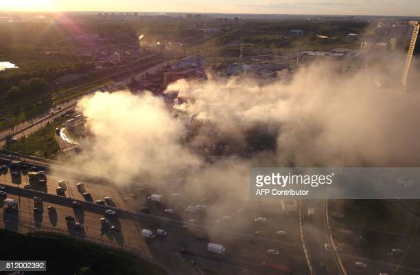 Smoke rises as firefighters and rescuers intervene at the Rio shopping mall in Moscow on July 10 2017 Ten people poisoned by smoke were hospitalised...