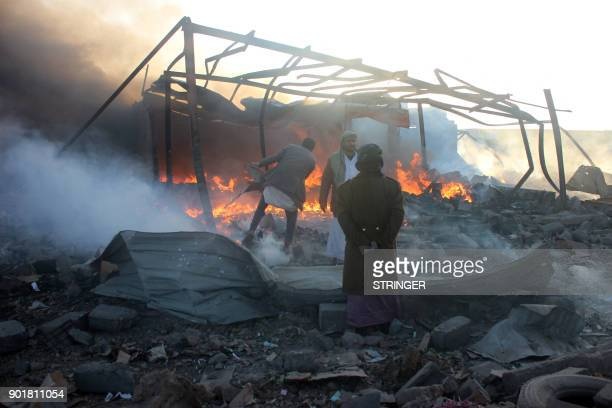 Smoke rises as Yemenis inspect the damage at the site of air strikes in the northwestern Huthiheld city of Saada on January 6 2018 / AFP PHOTO /...