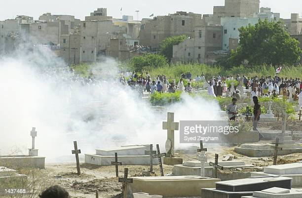 Smoke rises at a cemetery where police fired teargas canisters at an angry Christian crowd who were protesting the September 25 killings of seven...