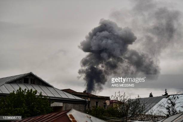 Smoke rises behind houses after shelling in the breakaway Nagorno-Karabakh region's main city of Stepanakert on October 7 during the ongoing fighting...