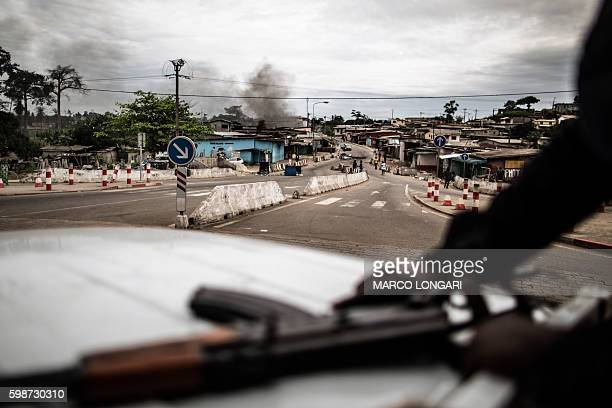 TOPSHOT Smoke rises from a barricade as Gabonese police officers patrol from a pick up in Libreville on September 2 2016 to try to secure...