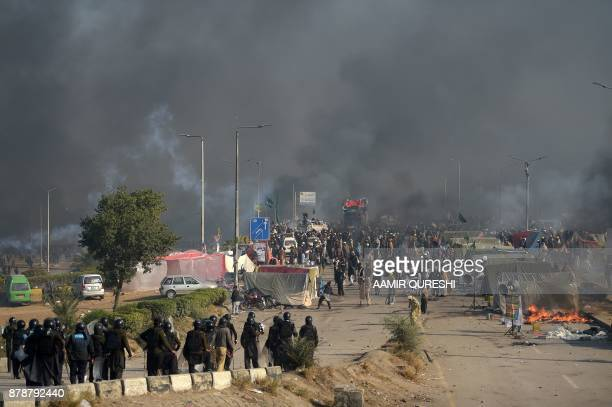 Smoke rises from a blocked flyover as protesters from the TehreekiLabaik Yah Rasool Allah Pakistan religious group clash with police in Islamabad on...