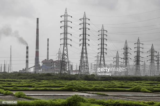 Smoke rises from a chimney as electricity pylons stand at the Tata Power Co Trombay Thermal Power Station in Mumbai India on Saturday Aug 5 2017...