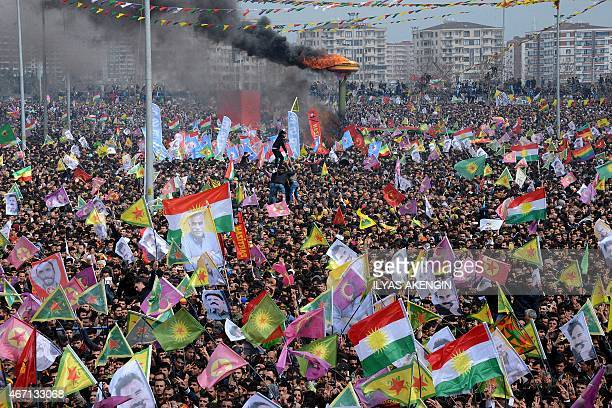 Smoke rises from a fire burning as people wave Kurdish flags and pictures of jailed Kurdish rebel leader Abdullah Ocalan as they gather to celebrate...