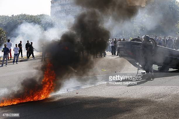Smoke rises from a fire burning next to a French CRS riot police officer standing near an overturned car as taxi drivers block Porte Maillot in Paris...