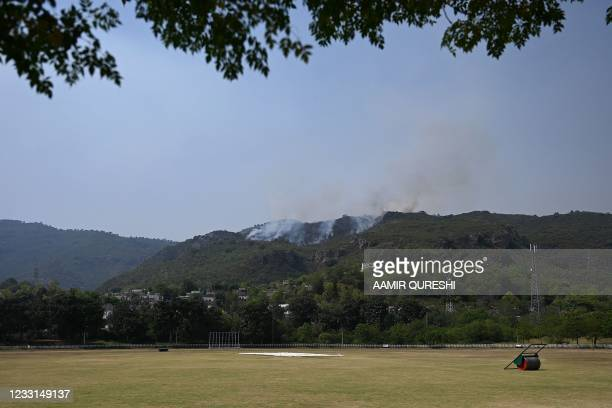 Smoke rises from a fire, which erupted on Margalla Hills due to rising temperatures near a cricket ground on a hot summer day near Saidpur village in...