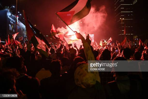 Smoke rises from a flare as people wave Palestinian flags during a protest against Israel in front of the Israeli Consulate in Istanbul, late on May...