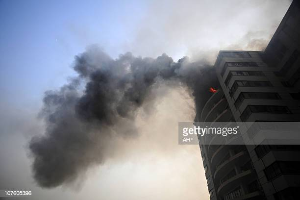 Smoke rises from a Hamim Group garment factory at Ashulia on December 14 2010 A raging fire on December 14 tore through a huge Bangladeshi garment...