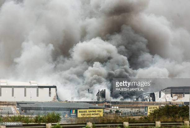 Smoke rises from a Makro building set on fire overnight in Umhlanga, north of Durban, on July 13, 2021 as several shops, businesses and...
