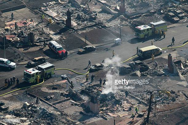 Smoke rises from a smoldering fire as firefighters sift through rubble at a burned home that was destroyed by a massive explosion and fire September...
