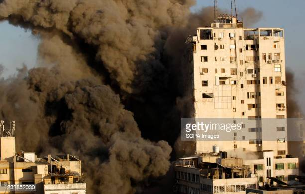 Smoke rises from a tower building destroyed by Israeli air strikes amid a flare-up of Israeli-Palestinian violence in Gaza City Israel carried out...