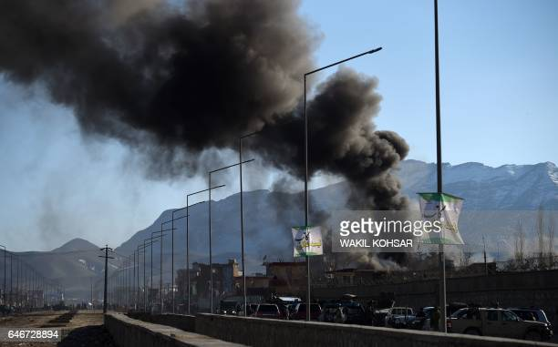 Smoke rises from an Afghan police district headquarters building after a suicide car bomb attack as a gun battle between Taliban and Afghan security...