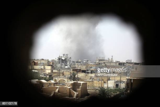 TOPSHOT Smoke rises from building in Raqa's eastern alSanaa neighbourhood on the edge of the old city on August 13 as Syrian Democratic Forces a US...