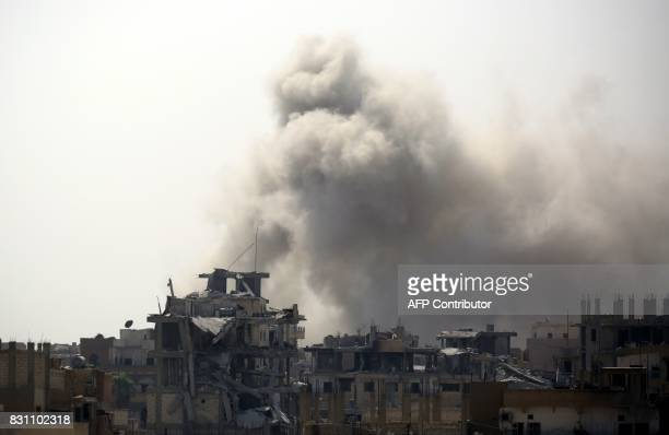 Smoke rises from building in Raqa's eastern alSanaa neighbourhood on the edge of the old city on August 13 as Syrian Democratic Forces a US backed...