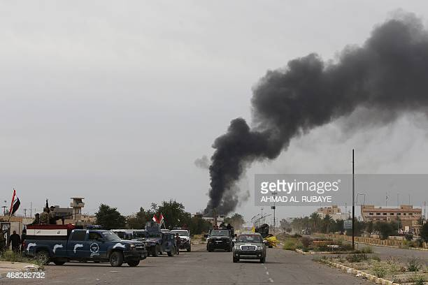 Smoke rises from buildings as Iraqi security forces patrol a street in Tikrit on April 1 a day after the prime minister declared victory in the...