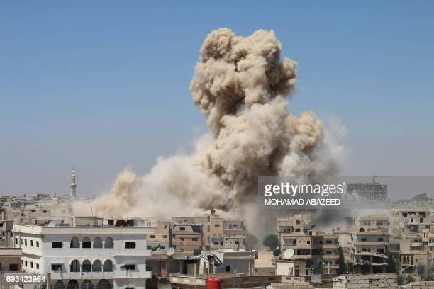 TOPSHOT Smoke rises from buildings following a reported air strike on a rebelheld area in the southern Syrian city of Daraa on June 7 2017 / AFP...