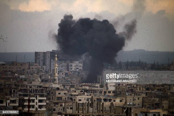 TOPSHOT Smoke rises from buildings following a reported regime surfacetosurface missile strike on a rebelheld area on the southern Syrian city of...