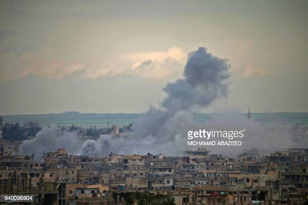 Smoke rises from buildings following a reported regime surfacetosurface missile strike on a rebelheld area on the southern Syrian city of Daraa on...