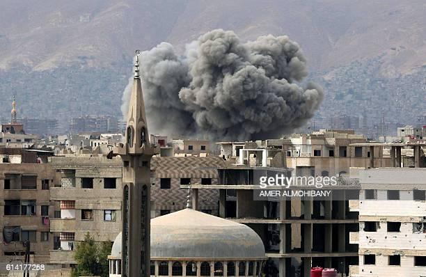 TOPSHOT Smoke rises from buildings following air strikes on Damascus' rebelheld eastern suburb of Zamalka on October 12 2016 CROP