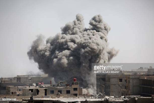 TOPSHOT Smoke rises from buildings following air strikes on Zamalka one of the few remaining rebelheld pockets in Eastern Ghouta on the outskirts of...