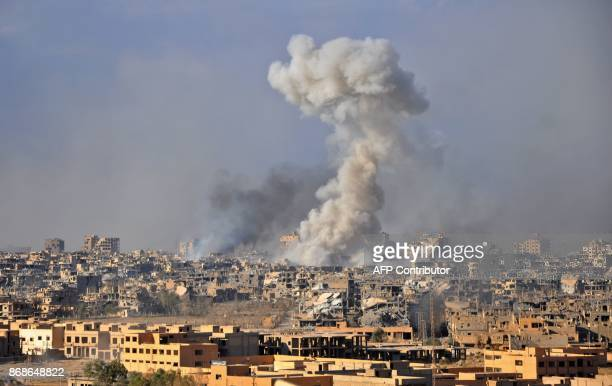 TOPSHOT Smoke rises from buildings following an air strike by Syrian government forces in the eastern city of Deir Ezzor on October 31 during an...