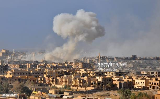 Smoke rises from buildings following an air strike by Syrian government forces in the eastern city of Deir Ezzor on October 31 during an operation...