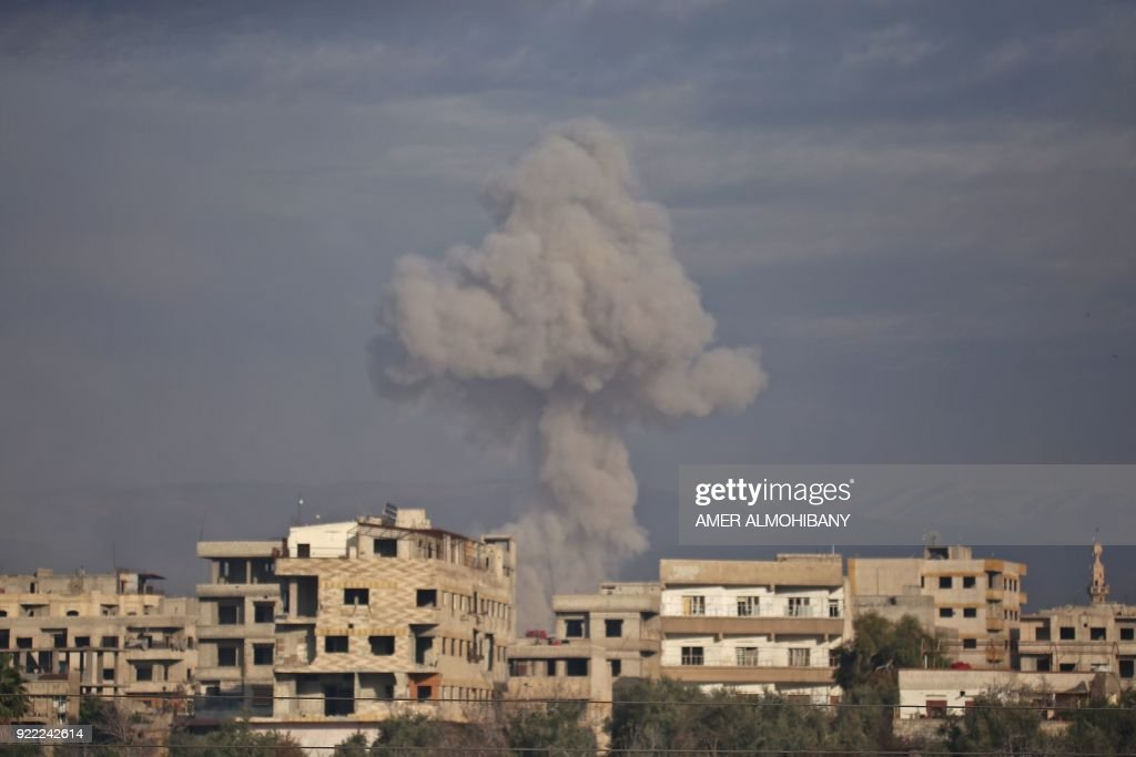 Smoke rises from buildings in Kafr Batna following Syrian government bombardments on the besieged Eastern Ghouta region on the outskirts of the capital Damascus on February 21, 2018. / AFP PHOTO / Amer ALMOHIBANY
