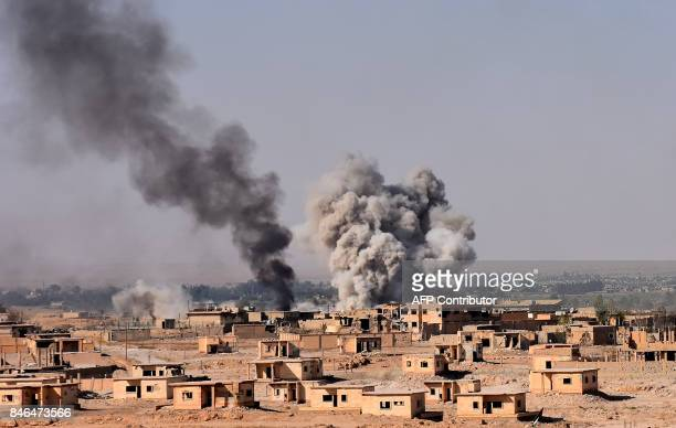 Smoke rises from buildings in the area of Bughayliyah on the northern outskirts of Deir Ezzor on September 13 as Syrian forces advance during their...
