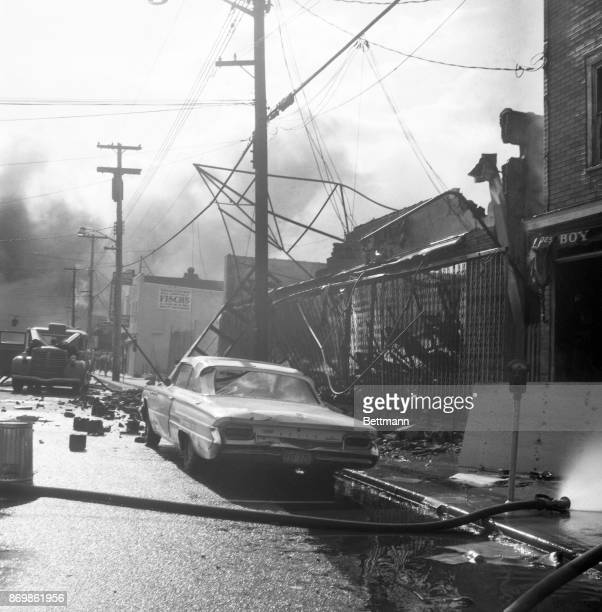Smoke rises from burning buildings in the background and gutted cars and stores loom in the foreground after mobs set fires and looted stores in the...