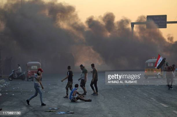 Smoke rises from burning tyres during as Iraqis demonstrate against state corruption failing public services and unemployment in the Iraqi capital...