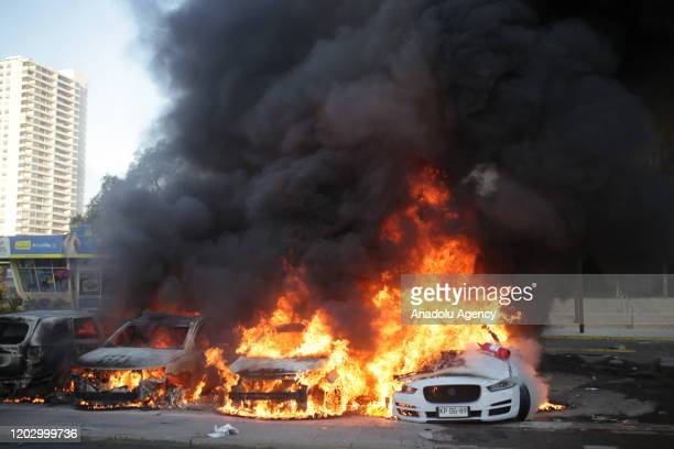 Smoke rises from burning vehicles during a protest against government at Vina del Mar Music Festival's opening in Vina del Mar, Chile on February 23,...