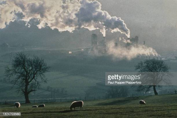 Smoke rises from chimneys at a timber processing and chipboard manufacturing plant and factory on the banks of the River Tyne at Hexham in...