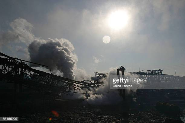 Smoke rises from embers after explosions in the Jilin Petroleum and Chemical Company on November 14 2005 in Jilin City some 100 km east from...