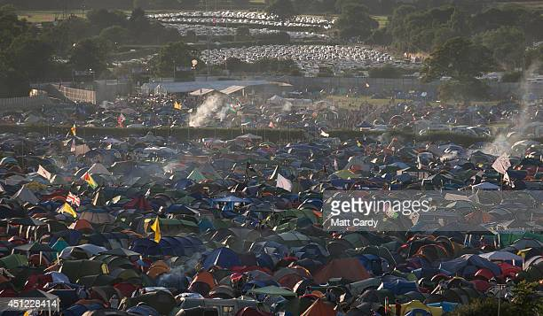 Smoke rises from festival revellers' tents pitched at Worthy Farm in Pilton on the first day of the 2014 Glastonbury Festival on June 25 2014 in...