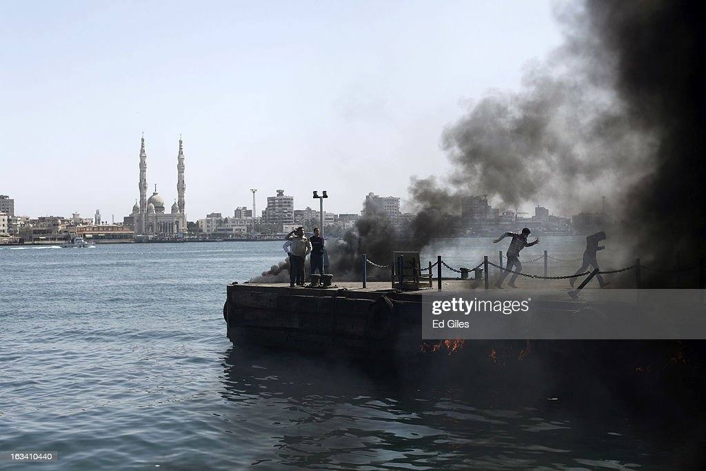 Smoke rises from fires set by protestors in an attempt to block boats from docking and disrupt traffic at the port on the Suez Canal to demonstrate after the announcement of the final verdict in the case of the Port Said football massacre, on March 9, 2013, in Port Said, Egypt. Over seventy football fans of the Al Masry team were killed during a stadium brawl that took place after a match between the Al Masry and Al Ahly teams in the northern Egyptian city in February 2012. Two senior police officers, the Port Said Security Director Essam Samak and head of the Port Said Water Bodies Security Department, Mohammed Saad, received 15 year sentences, while seven other police officers were acquitted. Five Port Said citizens received life sentences on Saturday, and twenty one civilian death sentences handed down in a January ruling on the same case were confirmed. (Photo by Ed Giles/Getty Images).