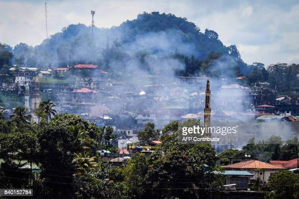 Smoke rises from houses as battles continue in Marawi on the southern island of Mindanao on August 28 2017 Soldiers killed 10 suspected militants on...
