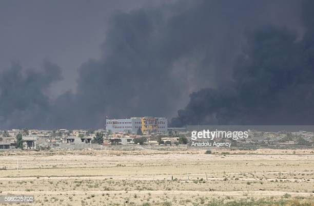 Smoke rises from oil wells sabotaged by Daesh terrorists as they were leaving Qayyarah Town recently freed from Daesh terrorists in Mosul Iraq on...