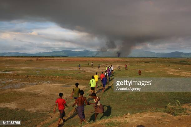 Smoke rises from Rohingya Muslims' houses as Rohingya Muslims flee from ongoing military operations in Myanmars Rakhine state into the Bangladesh...