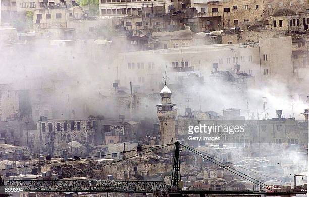 Smoke rises from several Palestinian buildings after Israeli Apache helicopters fired missiles April 7 2002 in the West Bank city of Nablus