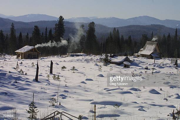 Smoke rises from snowcovered houses March 1 2002 in Sun City eastern Siberia The village was founded in 1994 near Lake Tiberkul by followers of...