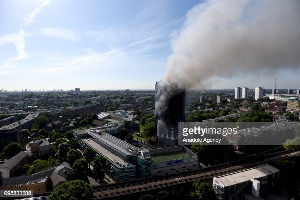 Smoke rises from the building after a huge fire engulfed the 24 storey residential Grenfell Tower block in Latimer Road West London in the early...