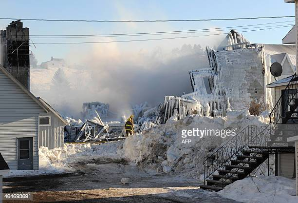 Smoke rises from the burnt remains of a retirement home in L'IsleVerte on January 23 2014 Firefighters searched the ashes of a Quebec retirement home...