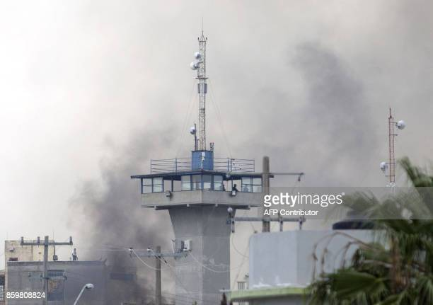 Smoke rises from the Cadereyta prison where a brawl among the prisoners left several wounded on October 10 2017 in Cadereyta Nuevo Leon Mexico / AFP...