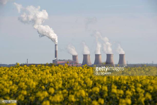 Smoke rises from the cooling towers of Cottam coal-fired power station, owned by EDF beyond a field of rapeseed near Darlton, east England on April...